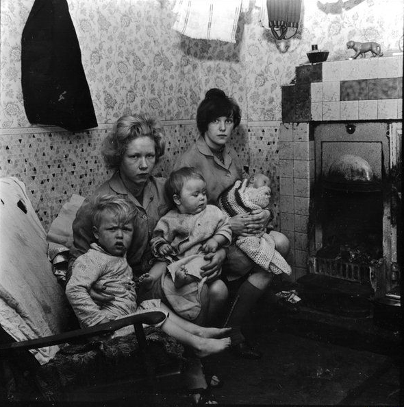 two mothers and children in living room with coal fire